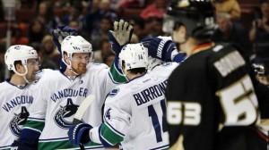 The Sedins and Alex Burrows celebrate a goal against the Anaheim Ducks.