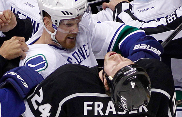 Henrik Sedin of the Vancouver Canucks in the middle of a scrum with Colin Fraser of the Los Angeles Kings.