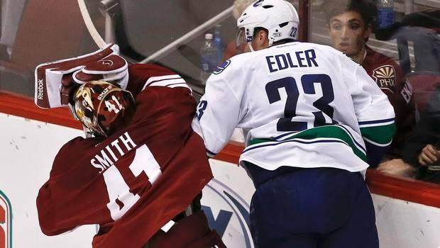 Alex Edler of the Vancouver Canucks crunches Phoenix Coyotes goaltender, Mike Smith