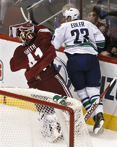 Alex Edler hits Mike Smith